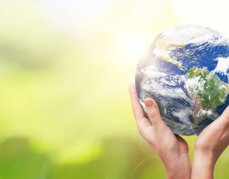 Hands holding the Earth in front of a green background