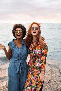 Two women laughing on the beach wearing dresses and sunglasses.