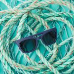 Sunglasses made from used ocean plastic resting on rope